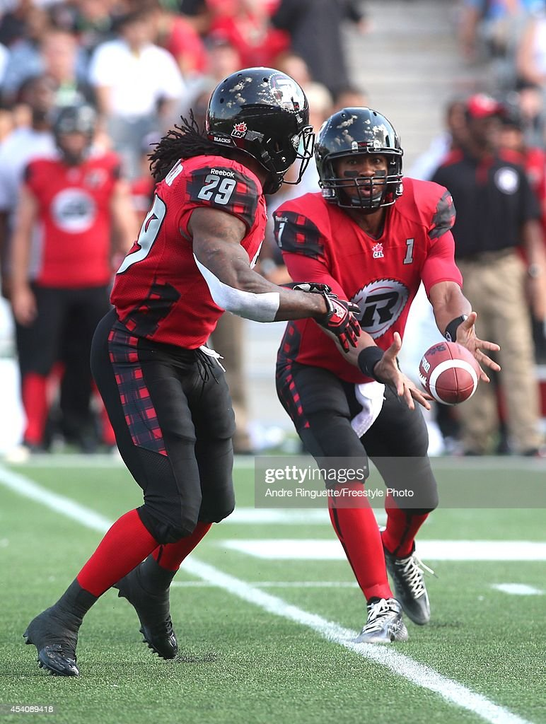 <a gi-track='captionPersonalityLinkClicked' href=/galleries/search?phrase=Henry+Burris&family=editorial&specificpeople=2664583 ng-click='$event.stopPropagation()'>Henry Burris</a> #1 of the Ottawa Redblacks hands the ball off to teammate Chevon Walker #29 the during a CFL game against the Calgary Stampeders at TD Place Stadium on August 24, 2014 in Ottawa, Ontario, Canada.