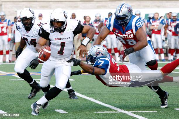 Henry Burris of the Ottawa Redblacks scrambles while being held by John Bowman of the Montreal Alouettes during the CFL game at Percival Molson...