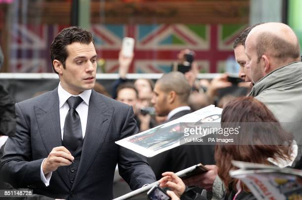 Henry Cavill signs autographs as he arrives for the European premiere of Man of Steel at the Odeon Leicester Square London