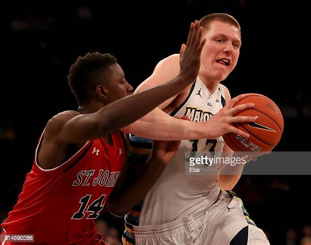 Henry Ellenson of the Marquette Golden Eagles tries to get past Kassoum Yakwe of the St John's Red Storm in the second half during the Big East...