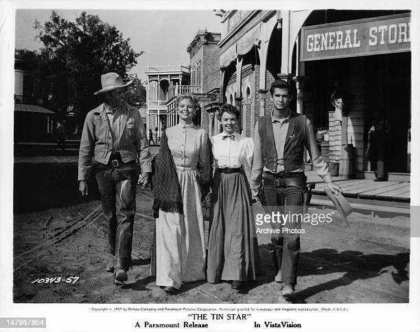 Henry Fonda Betsy Palmer Mary Webster and Anthony Perkins walking together in the town square in a scene from the film 'The Tin Star' 1957