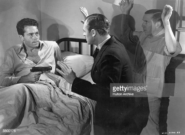 Henry Fonda points a gun at Jerome Cowan and the shadowy figure of a third man in a scene from the film 'You Only Live Once' a melodrama based...