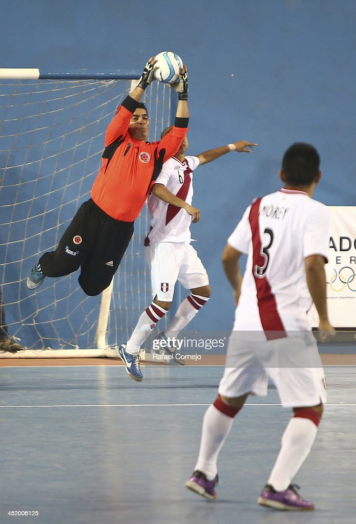 Henry Gomez of Colombia fights for the ball with <a gi-track='captionPersonalityLinkClicked' href=/galleries/search?phrase=Jorge+Aguilar&family=editorial&specificpeople=857548 ng-click='$event.stopPropagation()'>Jorge Aguilar</a> of Peru during a match between Colombia and Peru as part of the XVII Bolivarian Games Trujillo 2013 at Videna San Luis on November 25, 2013 in Lima, Peru.