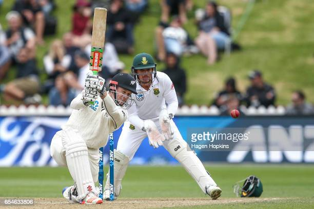 Henry Nicholls of New Zealand bats while Quentin de Kock of South Africa looks on during day three of the test match between New Zealand and South...