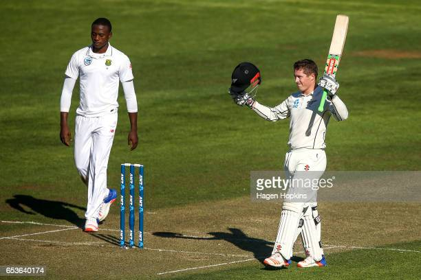 Henry Nicholls of New Zealand celebrates his century while Kagiso Rabada of South Africa looks on during day one of the Test match between New...