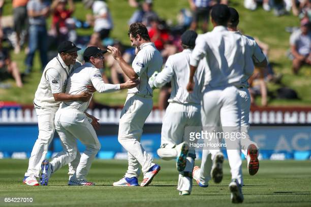 Henry Nicholls of New Zealand is congratulated by teammates Jeetan Patel and Colin de Grandhomme after taking a catch to dismiss Hashim Amla of South...