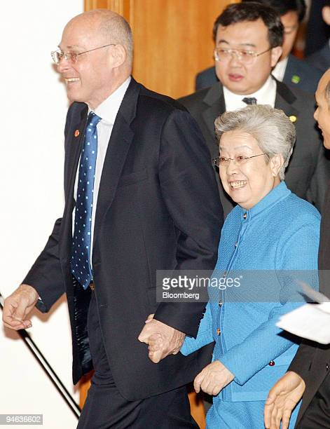 Henry Paulson US treasury secretary left and Wu Yi China's vice premier right hold hands as they walk to a joint briefing at the end of their...