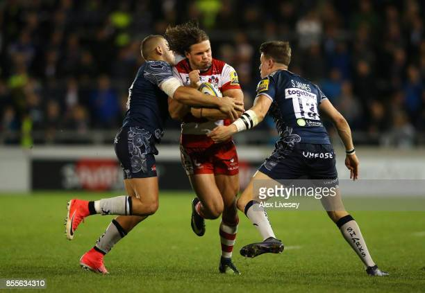 Henry Purdy of Gloucester Rugby is tackled by Mark Jennings and Sam James of Sale Sharks during the Aviva Premiership match between Sale Sharks and...