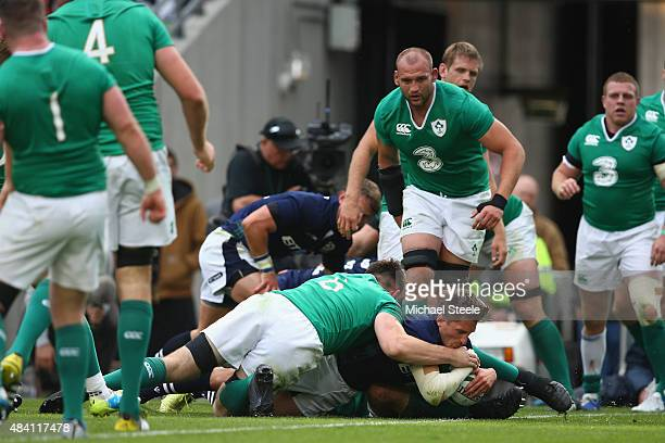 Henry Pygros of Scotland scores his sides second try despite the attention of Jack Conan of Ireland during the International match between Ireland...
