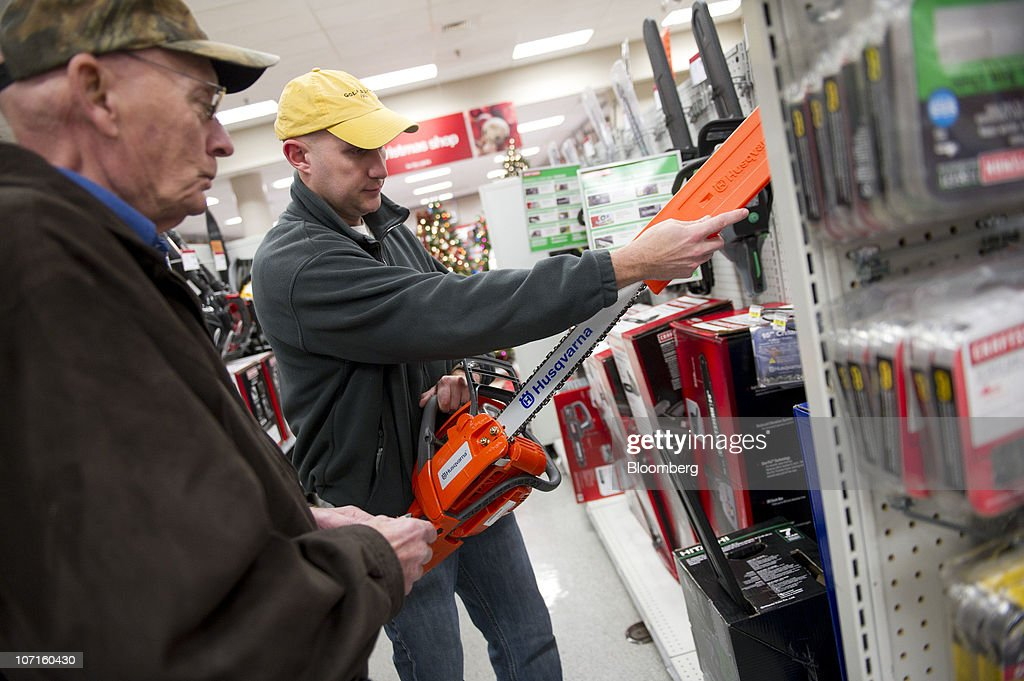 Henry Rogers, center, looks over a chainsaw with his dad Jeremy Rogers in a Sears store at Simon Property Group's Great Lakes Mall in Mentor, Ohio, U.S., on Friday, Nov. 26, 2010. Shoppers on Black Friday, the biggest shopping day of the year, are taking advantage of deals as they face down a slower economic recovery than projected. Photographer: Daniel Acker/Bloomberg via Getty Images