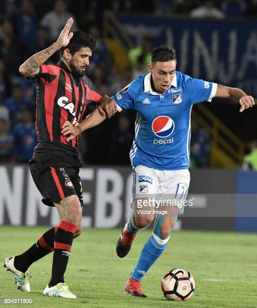 Henry Rojas of Millonarios fights for the ball with Luis González of Atletico Paranaense during a match between Millonarios and Atletico Paranaense...
