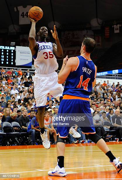 Henry Sims of the Philadelphia 76ers takes a shot over Jason Smith of the New York Knicks during a preseason game at the Carrier Dome on October 14...