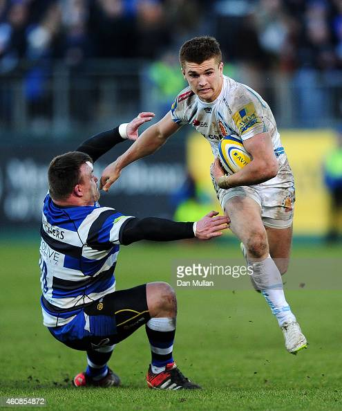 Henry Slade of Exeter Chiefs hands off David Wilson of Bath during the Aviva Premiership match between Bath Rugby and Exeter Chiefs at Recreation...