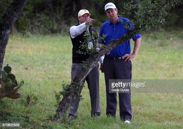 J Henry speaks with a rules official before playing his shot out of the rough on the fifth hole during the first round of the Valero Texas Open at...