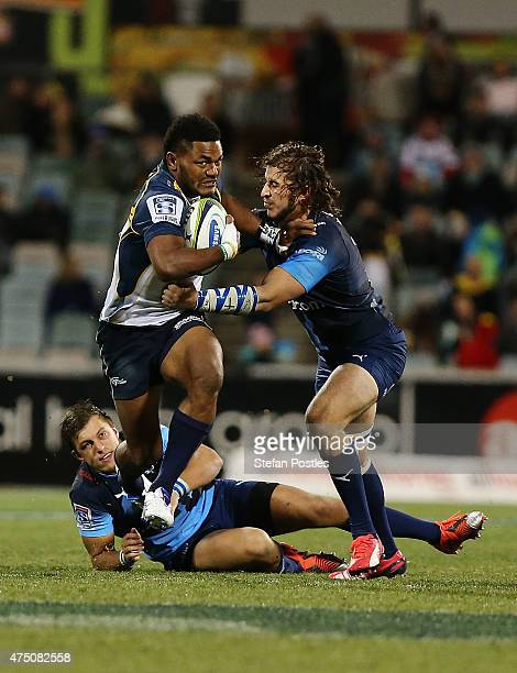 Henry Speight of the Brumbies pushes off two Bulls players to score a try during the round 16 Super Rugby match between the Brumbies and the Bulls at...