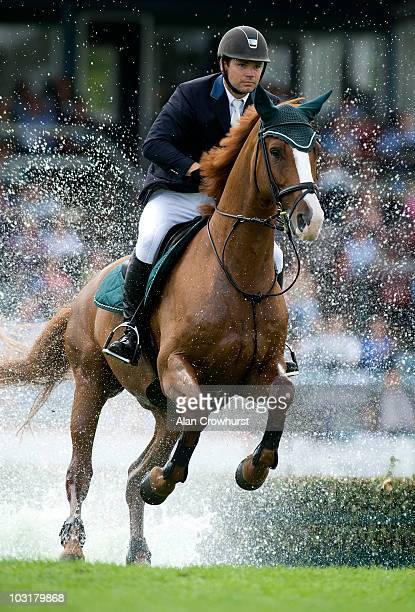 Henry Turrell of Great Britain riding Ahorn Van De Zuuthoeve splash their way through the water jump in The Old Lodge Queen Elizabeth II Cup during...