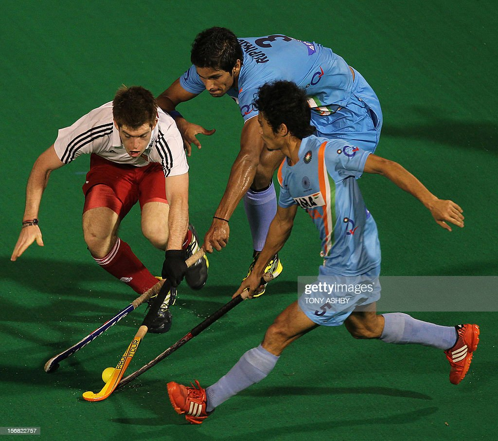 Henry Weir of England (L) contests Pal Singh Rupinder (C) and Kotharjit Singh Khadangbam (R) of India during their men's match at the International Super Series hockey tournament in Perth on November 22, 2012. AFP PHOTO/TONY ASHBY -- IMAGE STRICTLY FOR EDITORIAL USE - STRICTLY NO COMMERCIAL USE