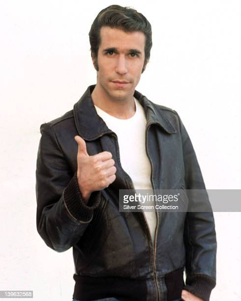 Henry Winkler US actor wearing a black leather jacket and white tshirt giving a thumbs up in a publicity portrait against a white background issued...
