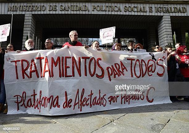 Hepatitis C sufferers and supporters hold a banner during a demonstration outside Spain's health ministry on December 27 2014 complaining they are...