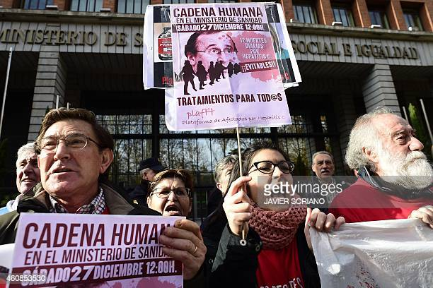 Hepatitis C sufferers and supporters hold placards during a demonstration outside Spain's health ministry on December 27 2014 complaining they are...