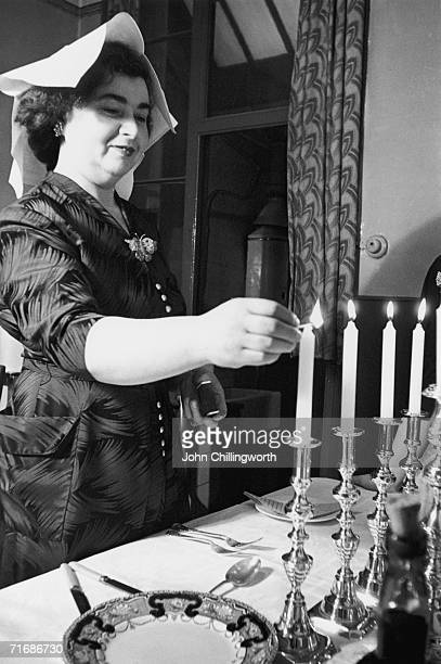 Her head covered by a napkin a Jewish mother in London's Whitechapel district lights the Sabbath candles at the climax of Passover 12th April 1952...