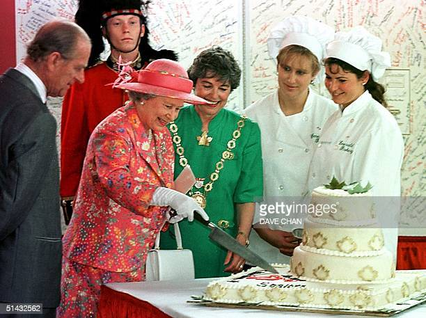Her Royal Highness Queen Elizabeth II cuts a 50th anniversary cake as The Duke of Edinburgh looks on at Aberdeen Pavilion in Ottawa Canada 01 July...