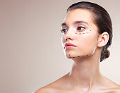 Studio shot of a beautiful young woman with cosmetic surgery markings on her face against a beige background