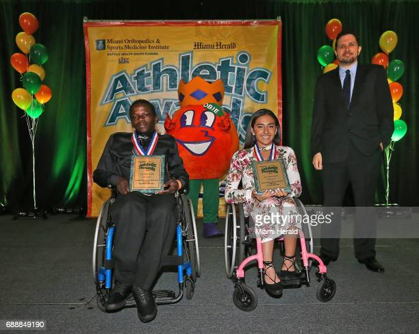 Herald sportswriter Andre Fernandez right presents the Leo Suarez/Walter Krietsch Courage Award to Fort Lauderdale High's Darrel Bouie Jr and Cypress...