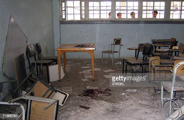 Afghan men look through the window of a classroom following a bomb blast at the Herat University 03 July 2006 A timebomb exploded in a classroom of...
