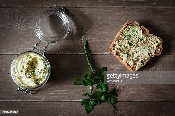 Herb butter, slice of spelt bread on wood