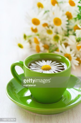 Herbal chamomile tea in a green cup : Stock Photo