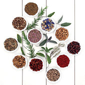 Herbal medicine selection also used in witches magical potions over distressed white wood background.