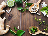 herbal pills in wooden spoon with ginger root, Kaffir lime fruit and flower on dark brown wood background with copy space. Above view.