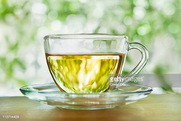 Herbal tea in a glass cup and saucer outdoors