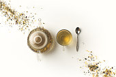 top view of fresh organic herbal tea in glass teapot and cup on white