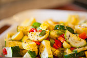 Serving bowl with herbed zucchini and yellow squash with sweet peppers
