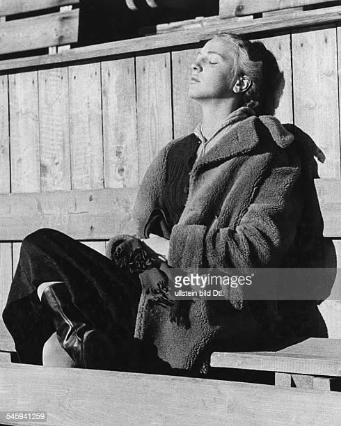 Herber Maxi *Eiskunstlaeuferin DOlympiasiegerin im Paarlauf mit Ernst Baier 1936 sitzt im Mantel auf einer Holzbank und sonnt sich 1937
