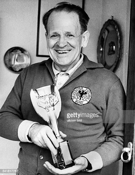 Herberger Josef *28031897Sportler Trainer Fussball D haelt zu Hause im DFBTrainingsanzug die ihm 1964 geschenkte Nachbildung des JulesRimetPokal in...