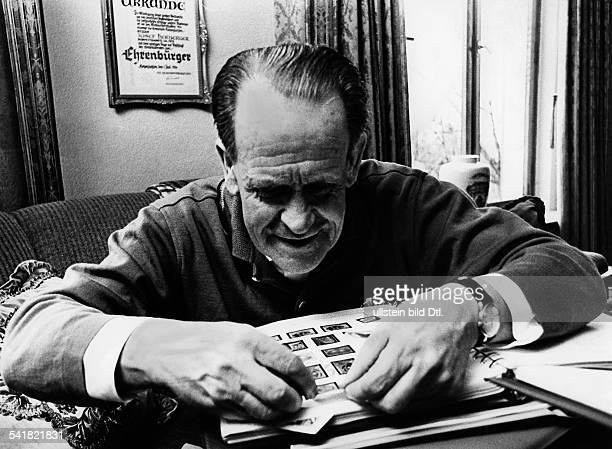 Herberger Josef *28031897Sportler Trainer Fussball D Herberger klebt Briefmarken in seinBriefmarkenAlbum an seinem Schreibtischhinten an der Wand...