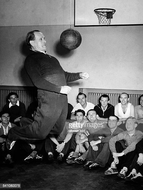 Herberger Josef *28031897Sportler Trainer Fussball D Waehrend die Nationalspieler auf dem Boden der Turnhalle sitzen fuehrt Herberger vor wie man den...
