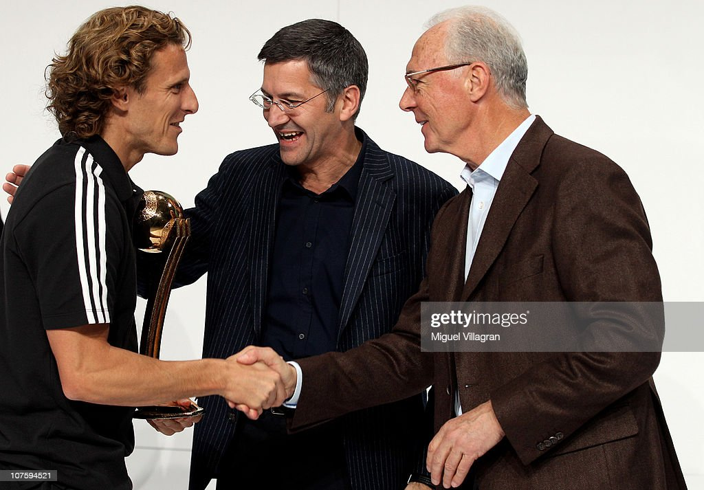 Herbert Hainer (C), the adidas Group CEO, and FIFA executive committee member Franz Beckenbauer (R) hand over the adidas Golden Ball award to Diego Forlan (L) during the FIFA 2010 World Cup adidas Golden Award ceremony at the adidas headquarters on December 14, 2010 in Herzogenaurach, Germany.