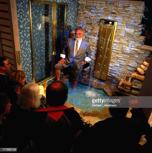 Herbert Kohler president and chairman of the Kohler Company standing in a small pool in a bathroom/shower display 1998 Shot for Business Week