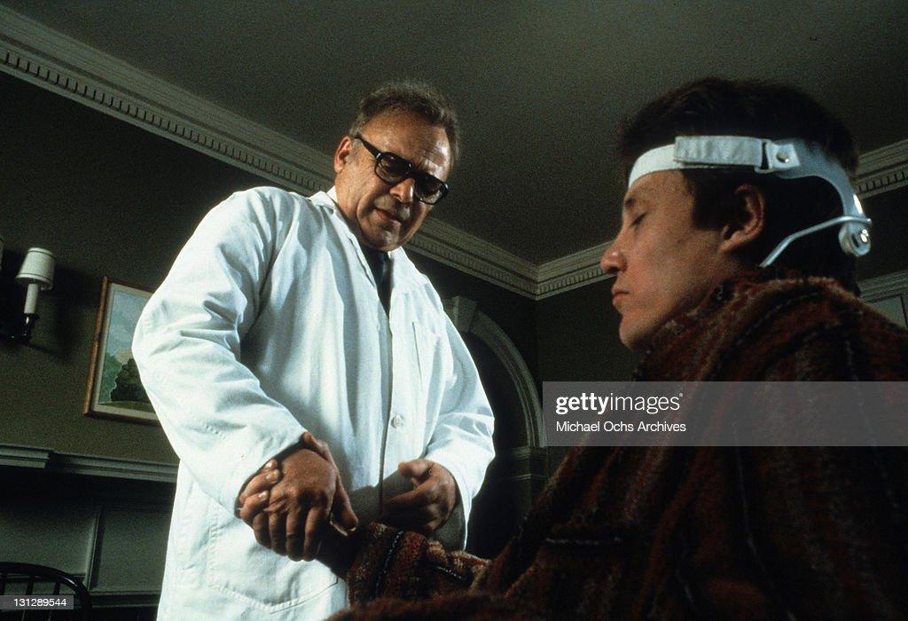 Herbert Lom checking Christopher Walken's wrist in a scene from the film 'The Dead Zone', 1983.