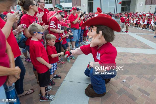 Herbie Husker fist bumps with a little fan before the game against the Arkansas State Red Wolves on September 02 2017 at Memorial Stadium in Lincoln...