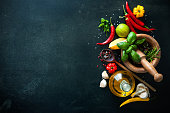 Herbs and spices with olive oil on slate background