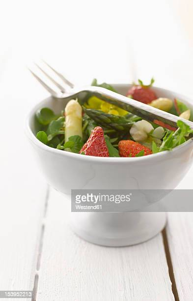 Herbs salad with asparagus and strawberries in bowl, close-up
