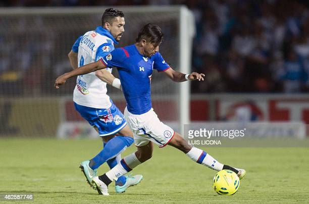 Hercules Gomez of Puebla vies for the ball with Joao Rojas of Cruz Azul during their Mexican Clausura tournament football match at the Cuauthemoc...