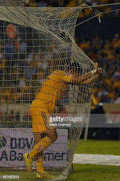 Hercules Gomez of Tigres holds the net during a match between Tigres UANL and Cruz Azul as part of 13th round Apertura 2014 Liga MX at Universitario...