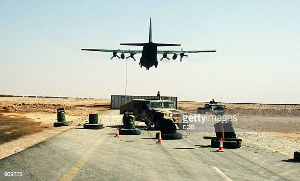 Hercules transport aircraft loaded with troops from the 101st Airborne Division takes off during Operation Desert Storm Behind the highway barricade...
