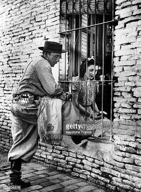 Here a gaucho wearing his sundaysuit visits his fiancee They talk through the windowgrate Note the artistic belt with silver coins and a poncho over...